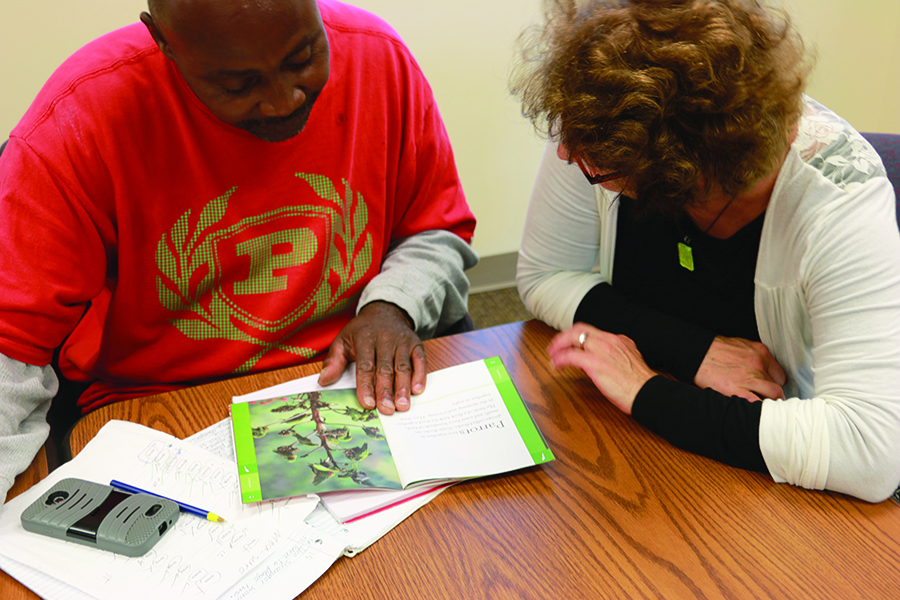 Man with Volunteer Mentor learning to read