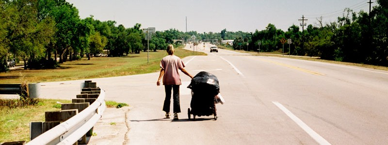 a homeless lady pulling a cart down the road